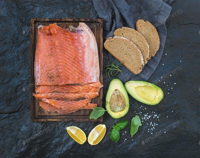 Smoked salmon filet with lemon, avocado, fresh herbs and bread