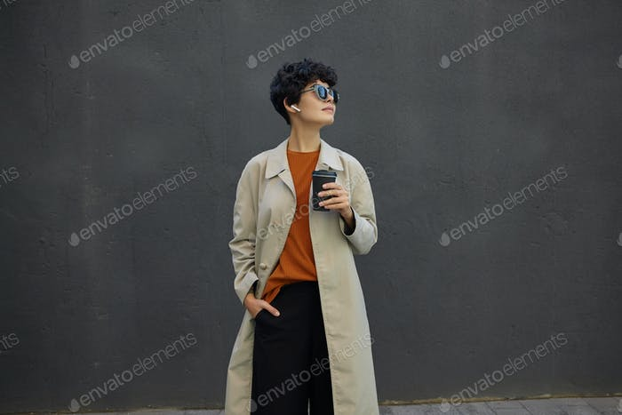 Good looking stylish young curly brunette lady with casual hairstyle drinking coffee outside