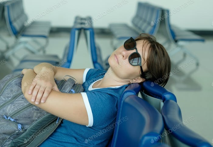 Tired caucasian woman sleeping in airport lounge waiting for flight