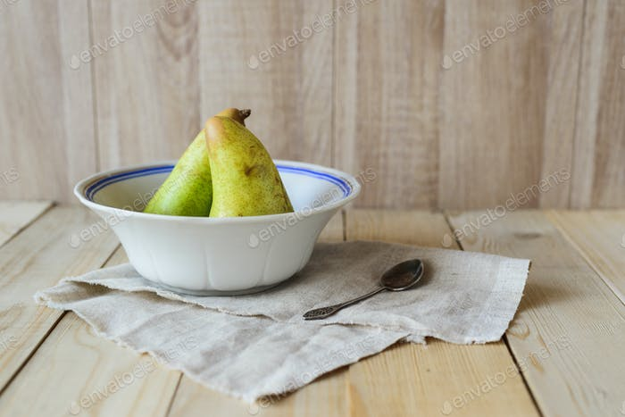 two pears in bowl on wooden background with copyspace