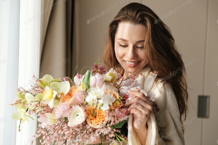 Smiling woman with bouquet of flowers at home