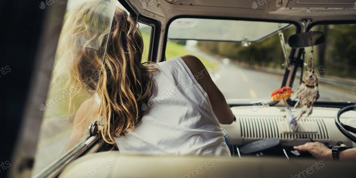Woman Sitting in a Car Put Head Out of Window Wind Blowing Her H