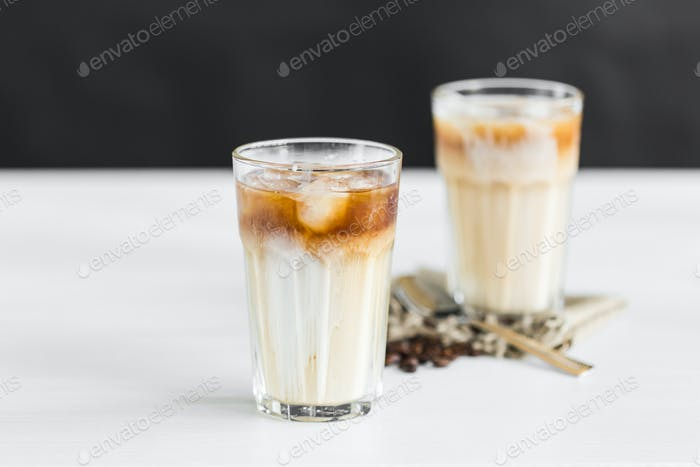 Ice coffee in a glass with cream over and coffee beans on the table