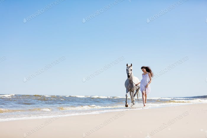 Young girl walking with white horse on the seashore.