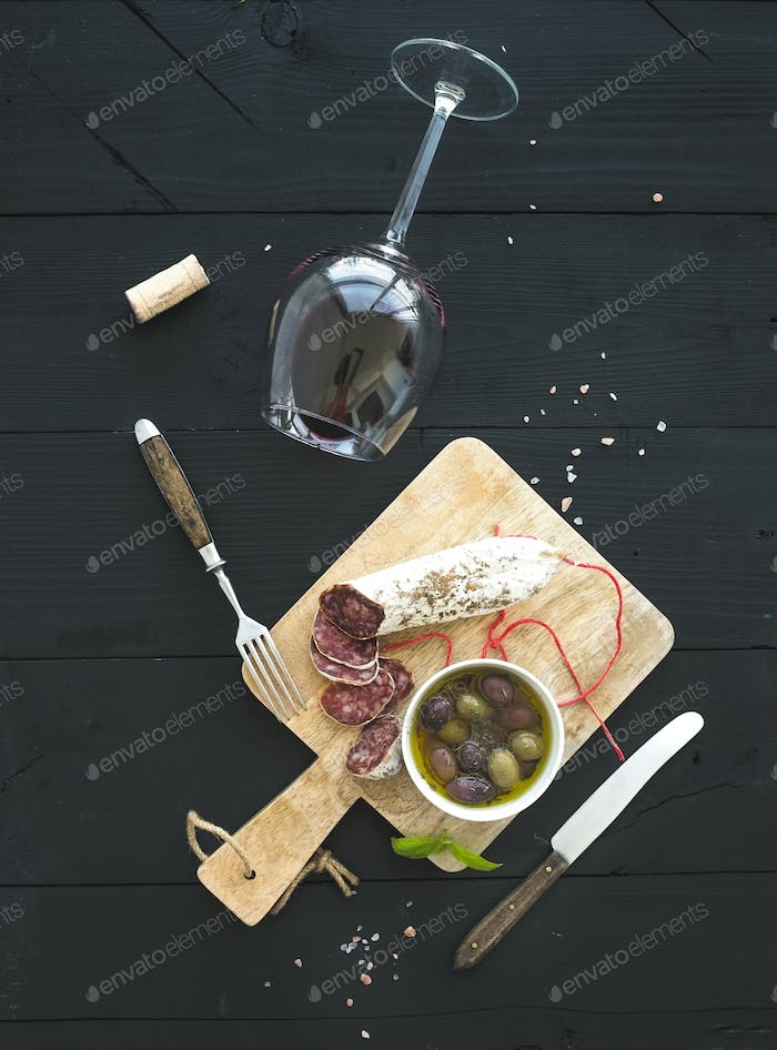 Wine appetizer set. Glass of red wine, French sausage and olives on black wooden backdrop, top view.
