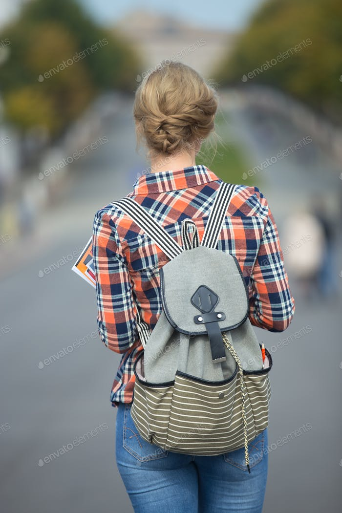 Young student girl walking down the street with a backpack
