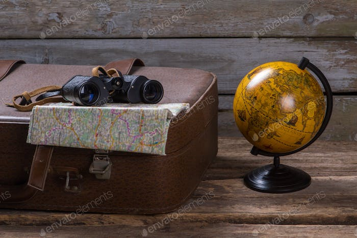 Binoculars and map on suitcase
