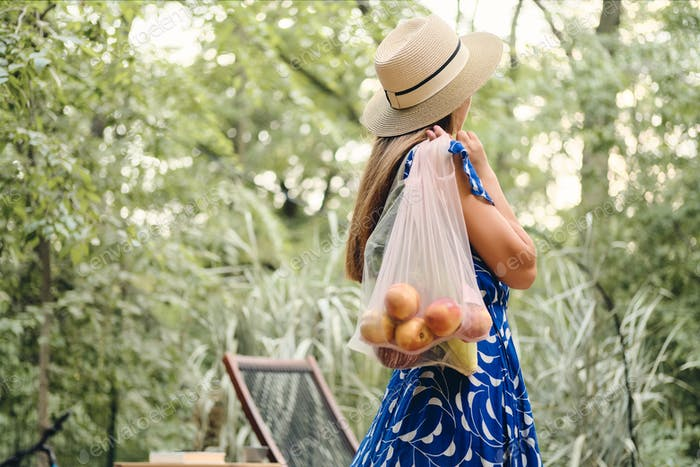 Young brown haired woman in dress and hat holding eco bag with fruits and vegetables in park