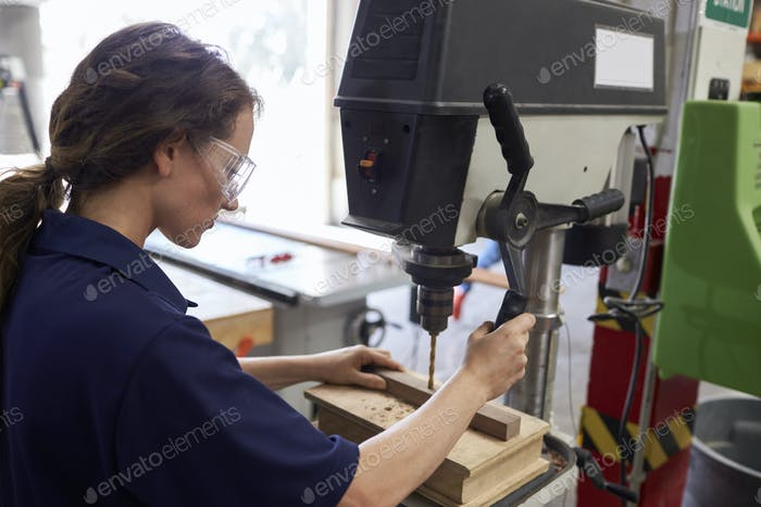 Female Engineer Using Drill In Factory