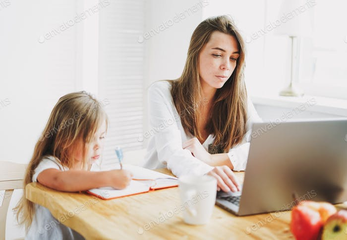 Working mom freelancer on laptop with little daughter