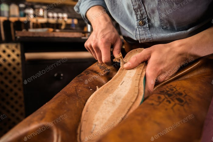 Shoemaker sitting in workshop making shoes