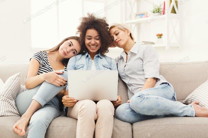 Three happy beautiful women using laptop at home