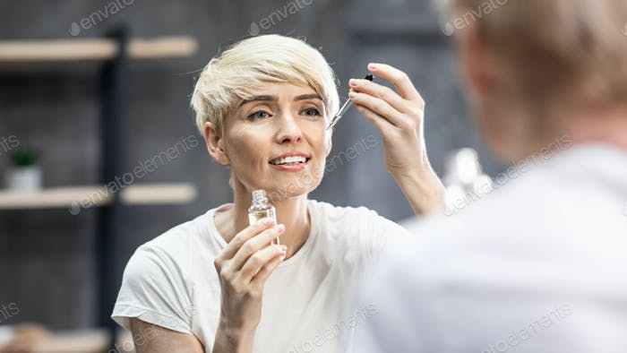 Lady Applying Cosmetic Oil Caring For Skin In Bathroom, Panorama