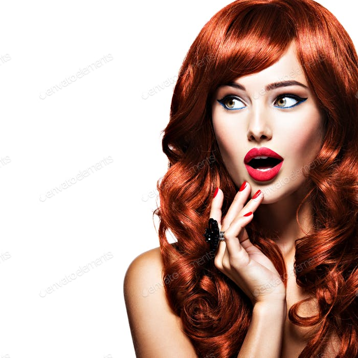 Beautiful surprised young woman very amazing looks away. Red hai