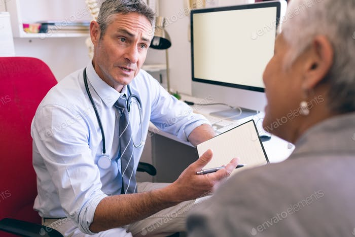 Male doctor and senior woman interacting with each other in clinic at retirement home