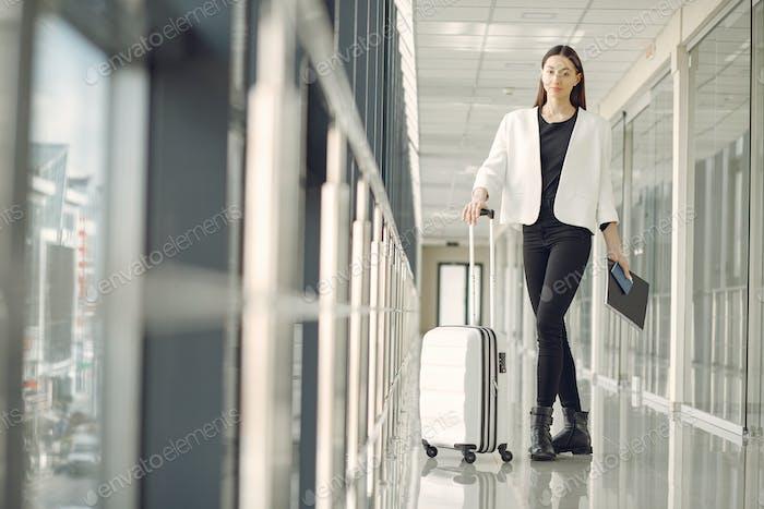 Frau mit Koffer am Flughafen