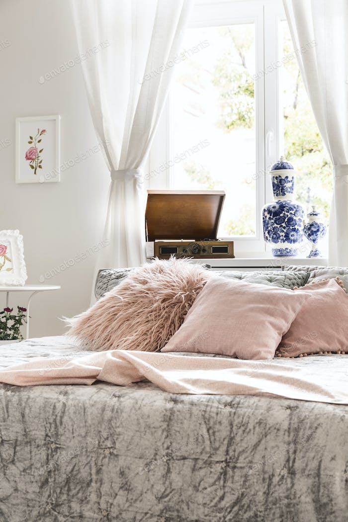 Pink pillows on bed in bright feminine bedroom interior with pos