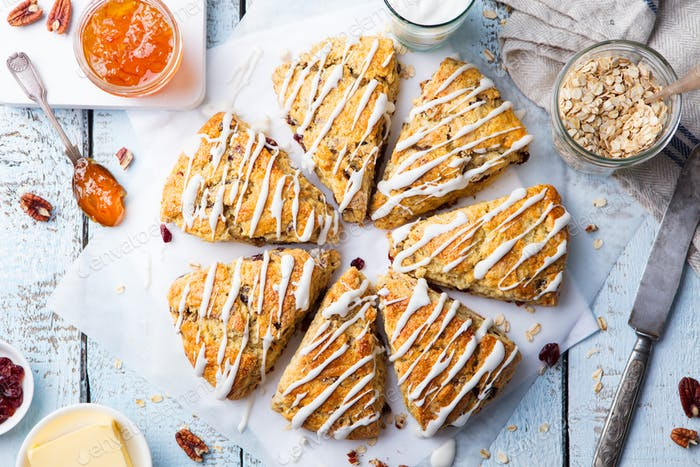 Scones with oats, cranberry and pecan nuts on wooden background. Top view.