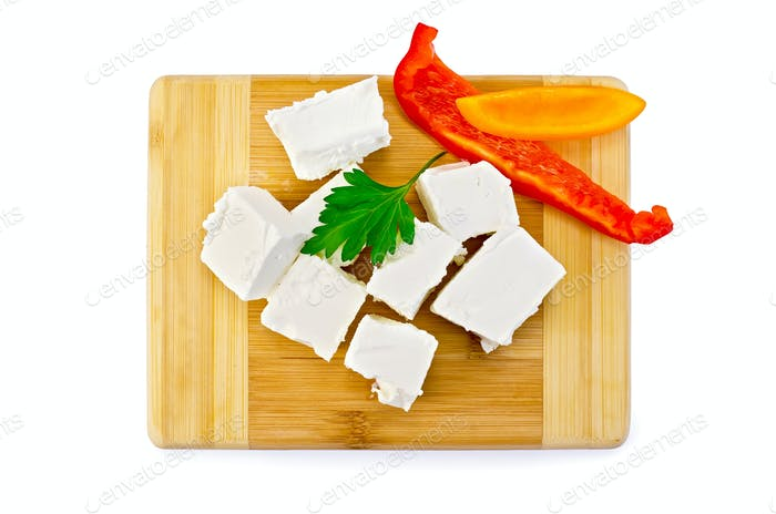 Feta cheese pieces on the board with pepper