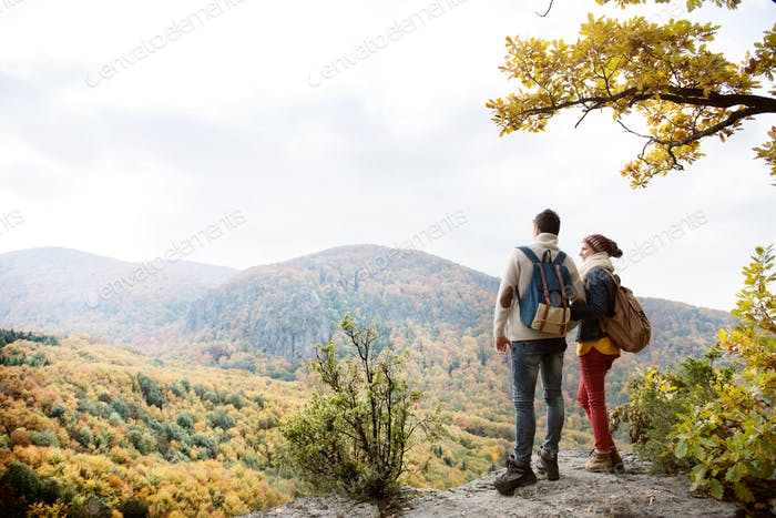 Thumbnail for Beautiful couple with backpacks against colorful autumn forest