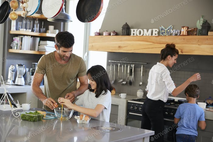Family In Kitchen Making Morning Breakfast Together
