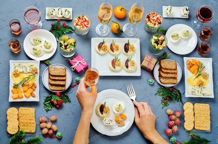 Christmas appetizers celebration table setting with woman's hand