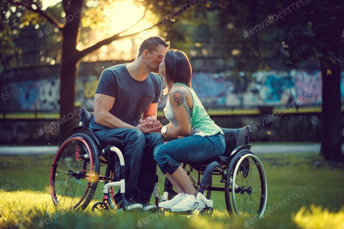 Handicapped young couple on two wheelchairs kissing .