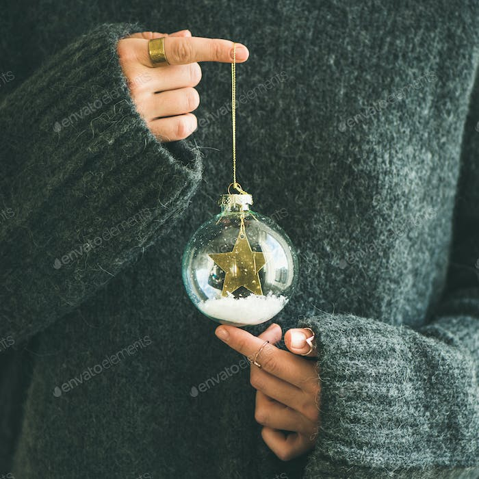 Woman in grey sweater holding decorative glass ball, square crop