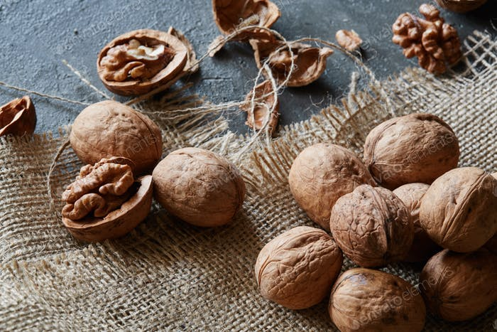 Walnuts and kernels with burlap fabric on a grey concrete backdrop