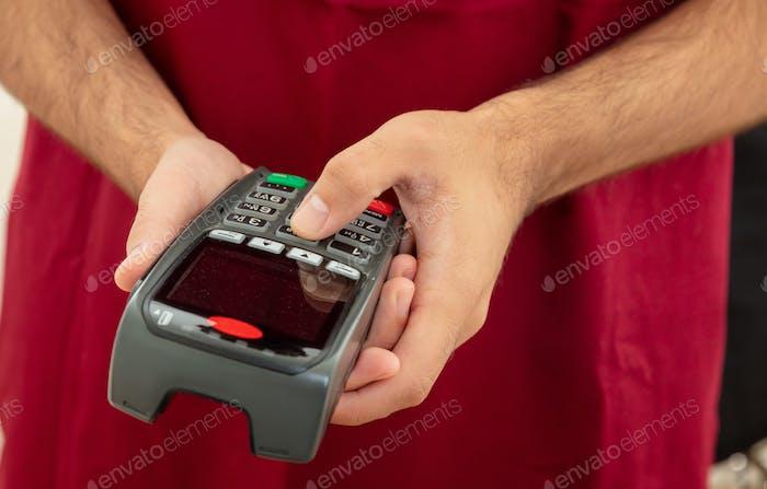 Man tippt auf einem POS-Terminal, Zahlung mit Kreditkarte. Bankwesen, Einkaufskonzept.