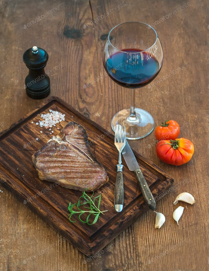 Cooked meat t-bone steak on serving board with garlic cloves and tomatoes