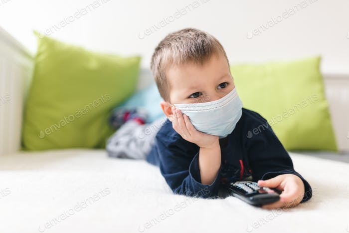 Unhappy child wearing respiratory mask as prevention against the Coronavirus Covid-19