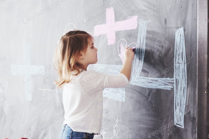 Curly little baby girl drawing with crayon color on the wall. Works of child