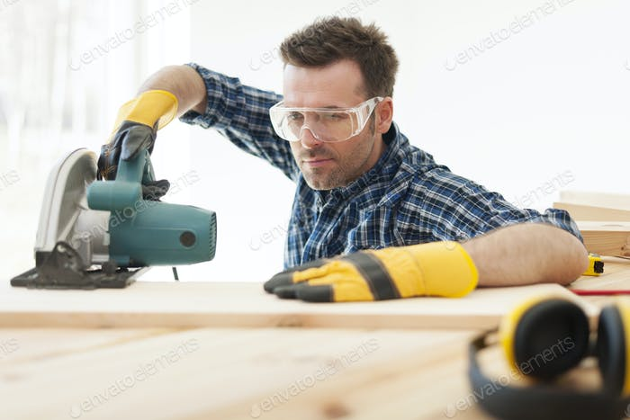 Focus carpenter cutting wooden plank