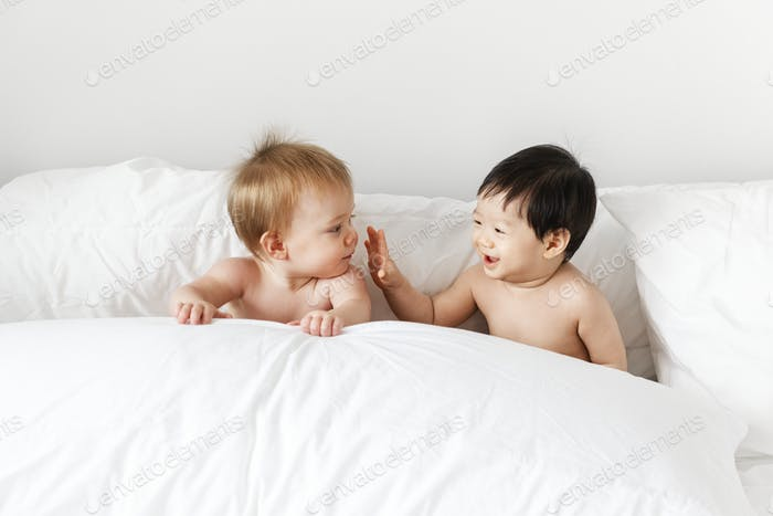 Babies playing on the bed