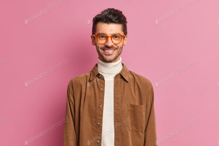 Handsome cheerful European guy with thick bristle smiles broadly wears optical spectacles and brown