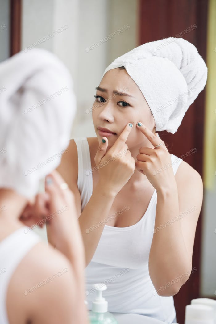 Asian woman popping pimple in bathroom