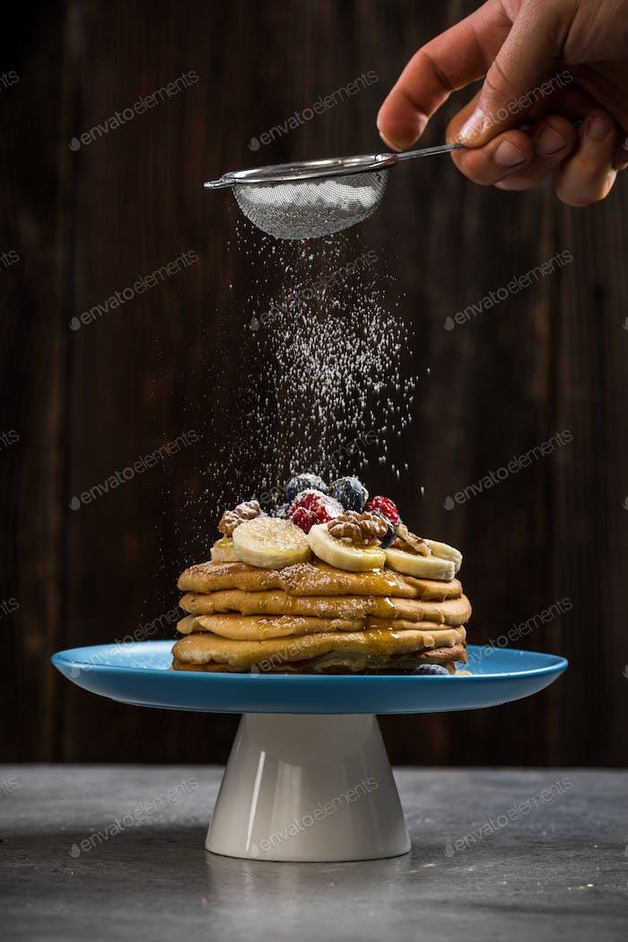 Sprinkling pancakes stack with sugar powder