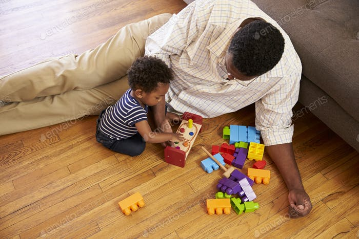 Grandfather And Grandson Playing With Toys On Floor At Home