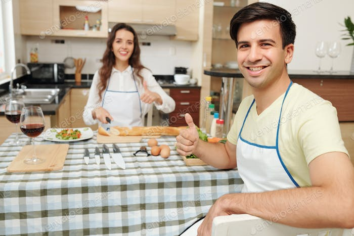 Cooking couple showing thumbs-up
