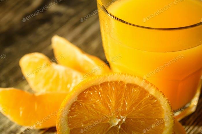 Orangen und Orangensaft auf einem hölzernen Hintergrund