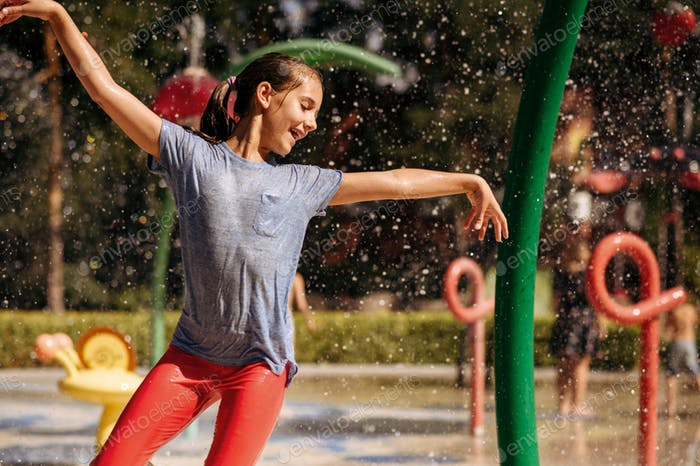 Little girl play with splashes on water playground