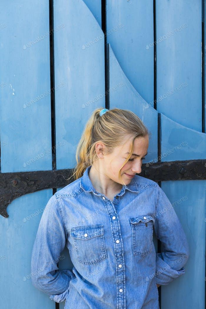 portrait of 13 year old girl against blue door.