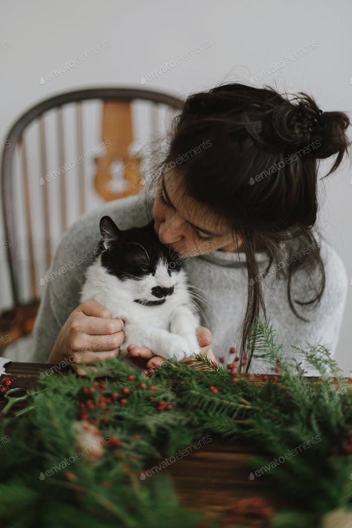 Cute cat helping woman making rustic christmas wreath. Authentic home moments, pet and holidays