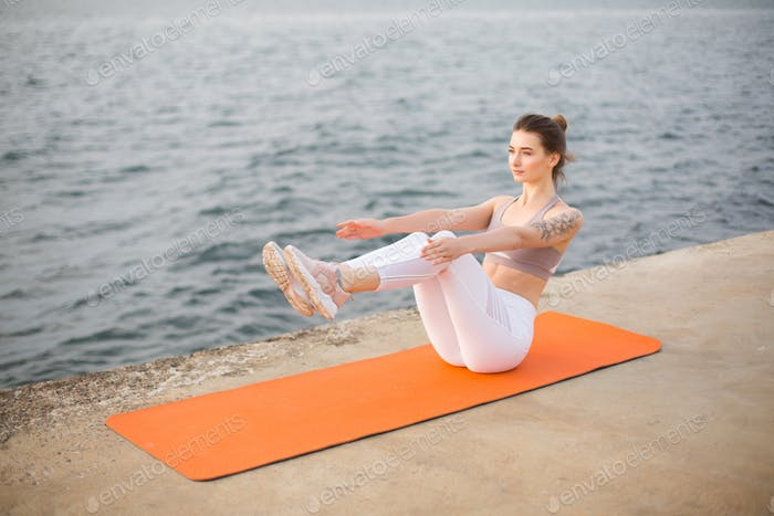 Young woman practicing yoga by the sea. Pretty girl in sporty to
