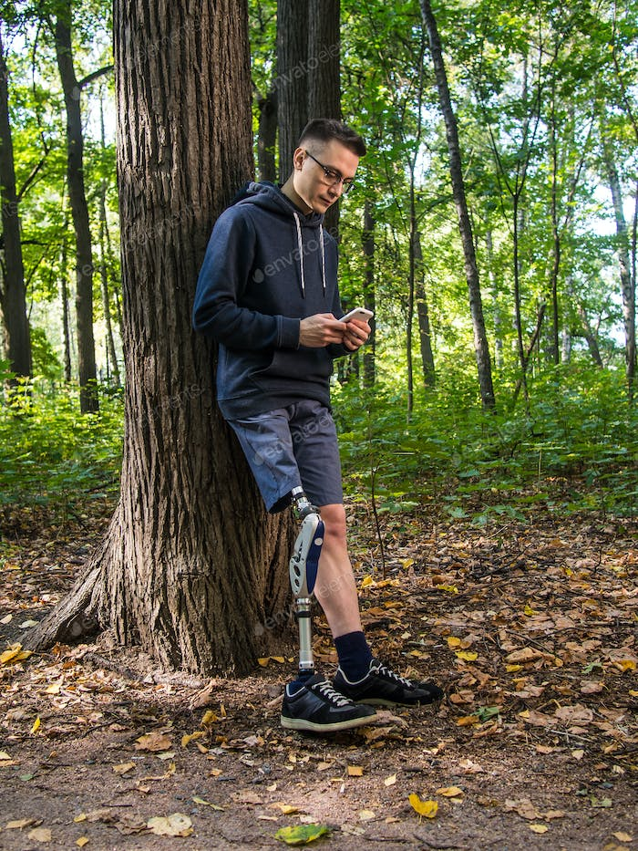 Young man with prosthetic leg using his smartphone