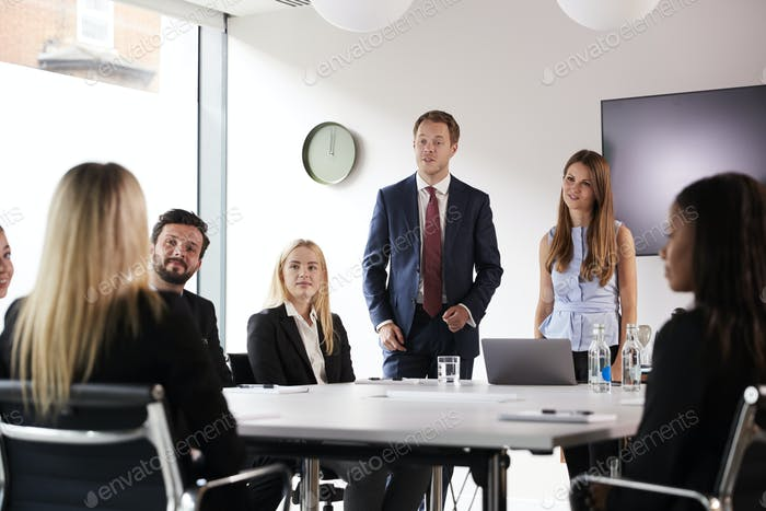 Group Of Young Businessmen And Businesswomen Meeting Around Table