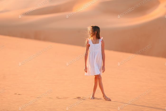 Girl among dunes in desert in United Arab Emirates