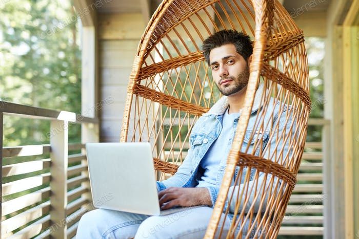 Content modern guy using pc outdoors