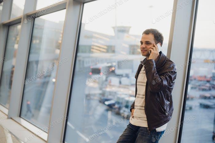 Hombre de Empresario hablando por teléfono en la terminal del aeropuerto